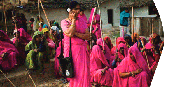 women gathered using cell phones to vote