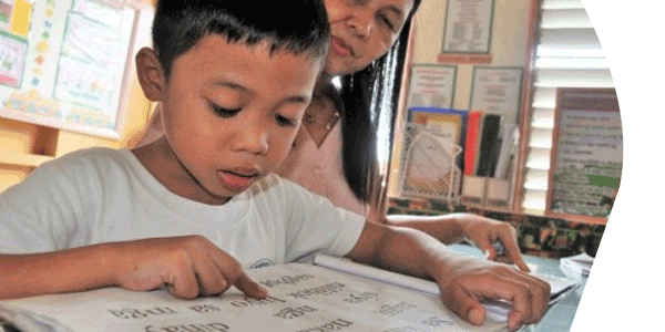 Teacher helping boy read in the Philippines