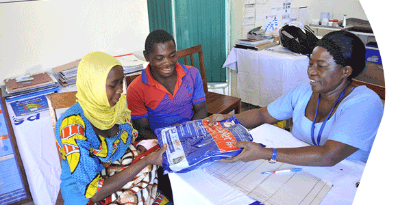 At the dispensary in Lwelu, Tanzania, Nurse Rehema Ngonyani distributes a mosquito net to clients Jaffar Ismaeli Liyoyo, 20, and his wife Fatuma Moussa Kanton, 19, with their one-week-old infant Noussofi.