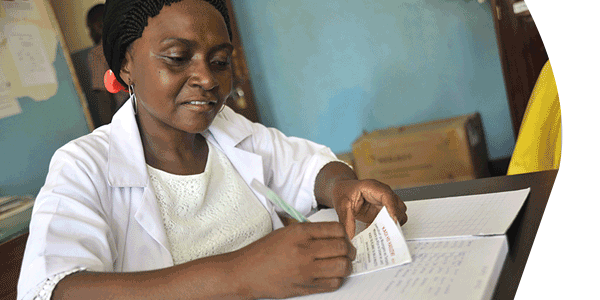 Nurse Pili Makota records client details prior to distributing a bed net at Naliendele Health Center in Tanzania.