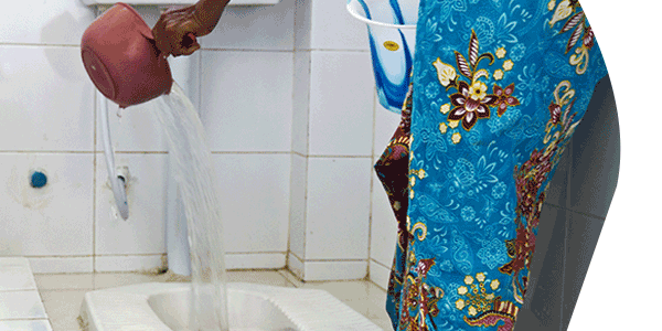 woman in colorful dress disposing waste water into toliet