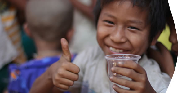smiling boy with a glass of drinking water with thumbs up